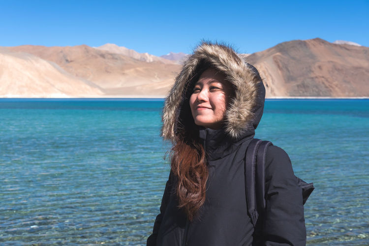 Smiling woman standing by lake against mountains