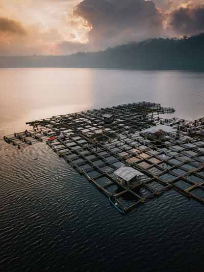 A local Balinese fishing structure sits in the middle of a large lake. One fisherman paddles out in a small kayak to check the structure and cast a fishing line. Aerial Shot Bali Drone  INDONESIA Abstract Aerial View Drone Photography Fish Mavic Pro Sunset Week On Eyeem The Great Outdoors - 2018 EyeEm Awards The Traveler - 2018 EyeEm Awards The Architect - 2018 EyeEm Awards Capture Tomorrow
