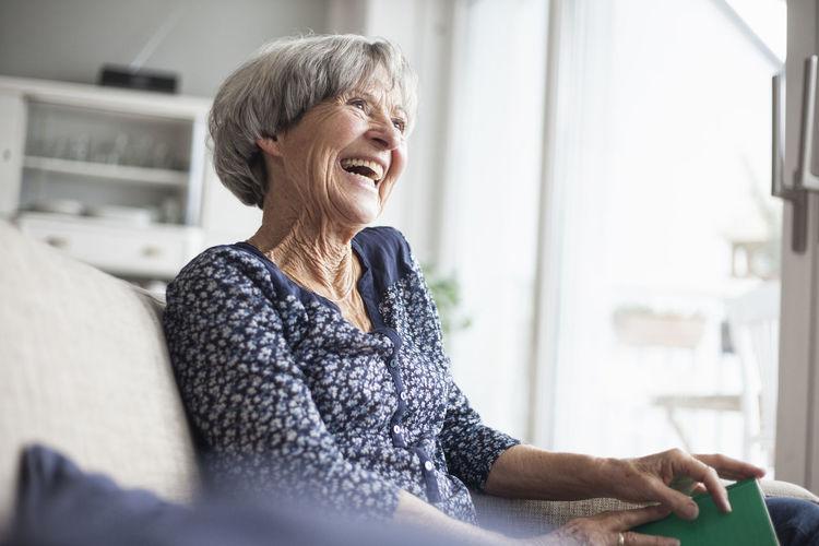 Woman looking at camera while sitting at home