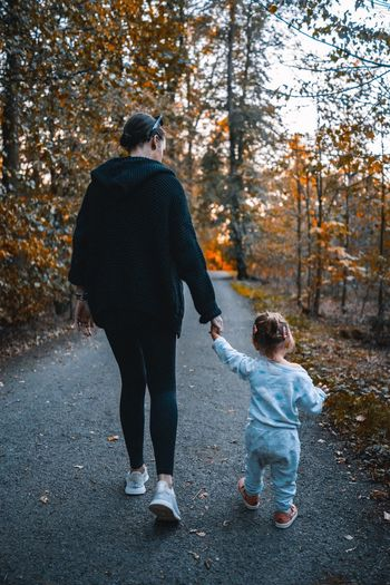 Autumn walk Parent Forest Walk Walking Autumn colors Autumn Full Length Two People Men Togetherness Change Tree Nature Rear View Love Plant Leisure Activity Bonding Lifestyles Casual Clothing Day Family Child Real People Positive Emotion