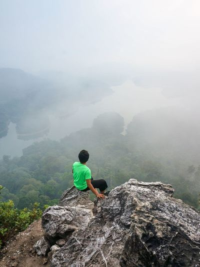 A young male hiker in green sit alone on the rock summit. Wonderful daybreak in mountains, heavy mist in deep valley. Beautiful morning scenery of rainforest from peak of Bukit Tabur in Malaysia Brave Determination Green Motivation Active Lifestyle  Adventure Beauty In Nature Bukit Tabur Courage Day Fog Hi Lake Landscape Lifestyles Malaysia Mist Mountain Nature Outdoors People Rainforest Scenics Summit Tranquility EyeEmNewHere Go Higher A New Beginning