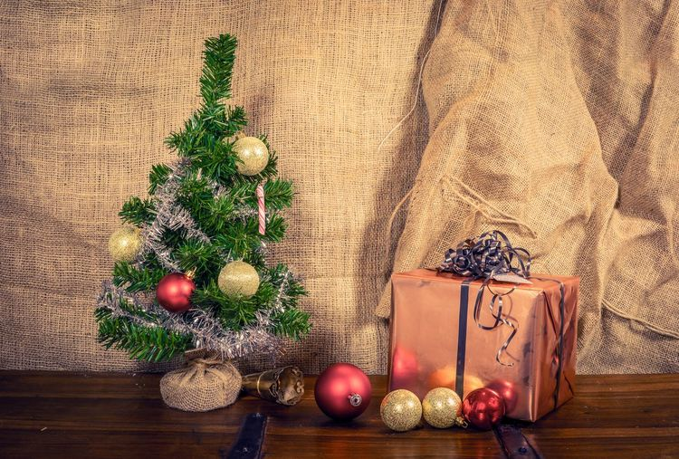 Small Christmas tree decorated with glittering Glass balls and a present on the wooden table Celebration Christmas Holiday Christmas Decoration Christmas Ornament Decoration Indoors  Wood - Material Still Life Holiday - Event christmas tree Tree No People Green Color Container Table Plant Celebration Event Gift Jute