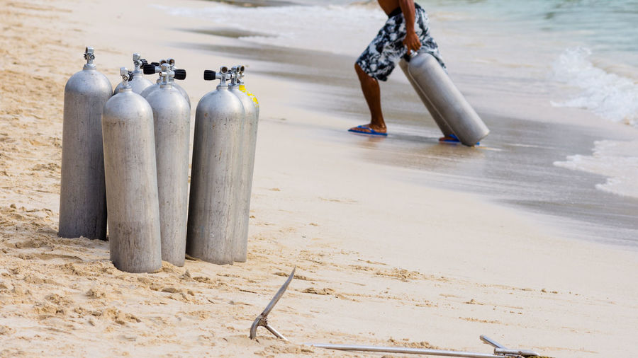 A collection of scuba divers air tanks on a tropical white sand beach. Tropical Paradise Waiting White Sand Beach Beach Day Diving Tanks Leisure Activity Outdoors People Sand Scuba Tanks Sea Tropical Climate Vacations Water