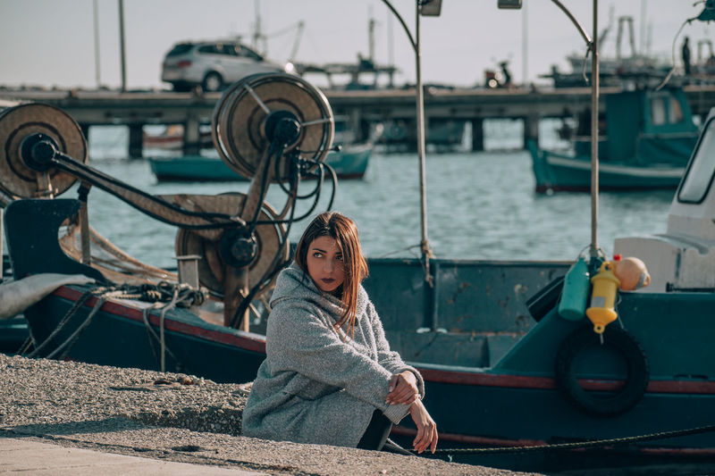 Woman looking away while sitting at harbor
