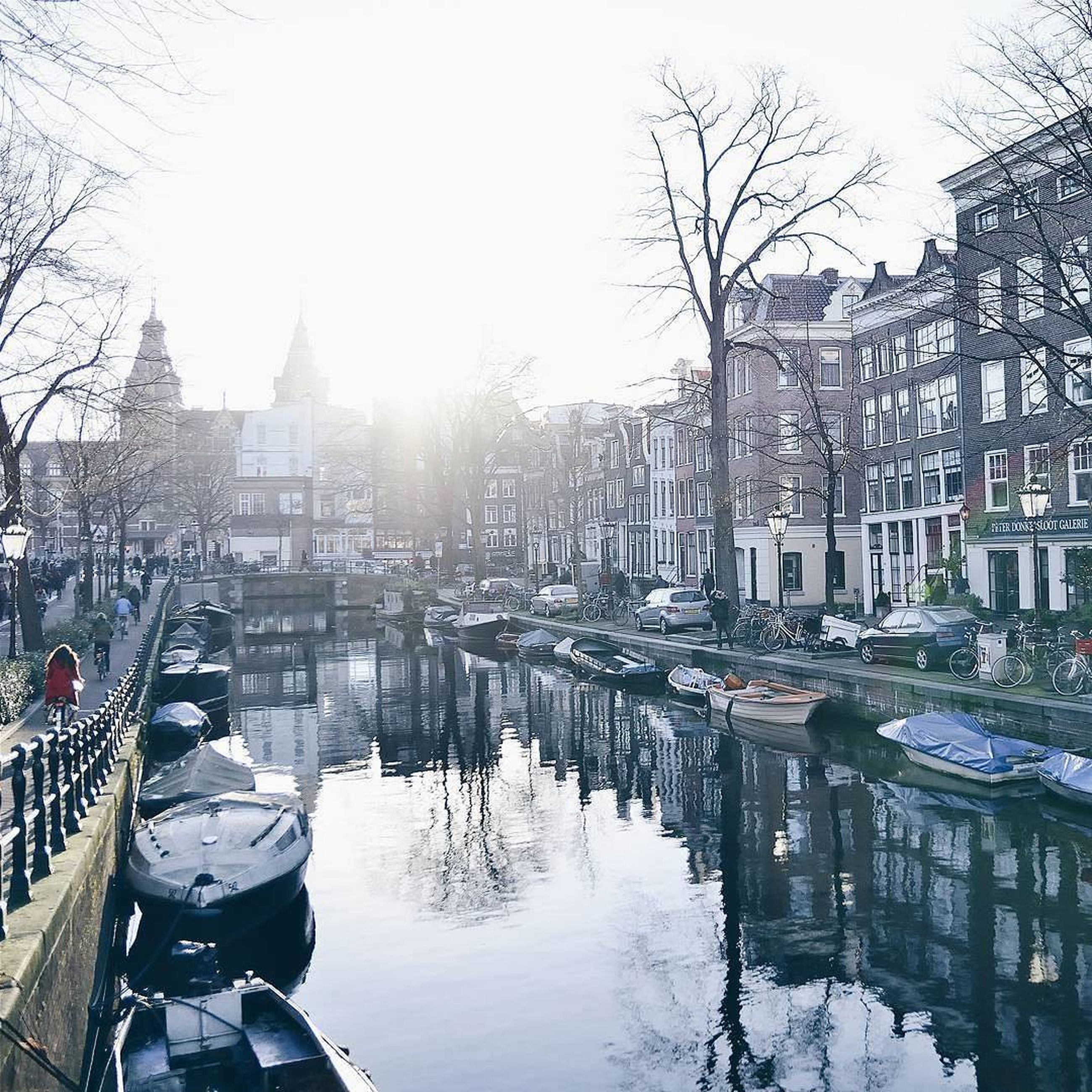 building exterior, architecture, built structure, winter, cold temperature, bare tree, snow, clear sky, city, water, tree, reflection, season, canal, river, weather, sky, day