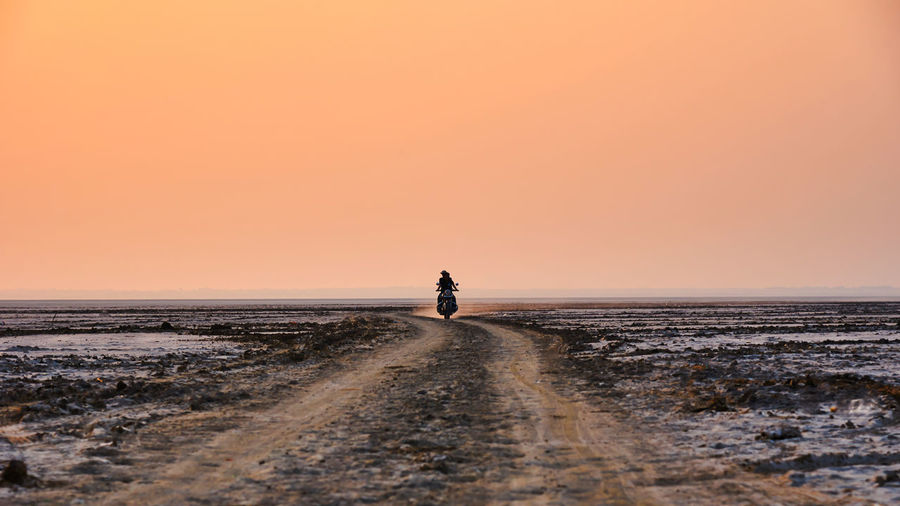 Person riding motorcycle on dirt road against sky during sunset