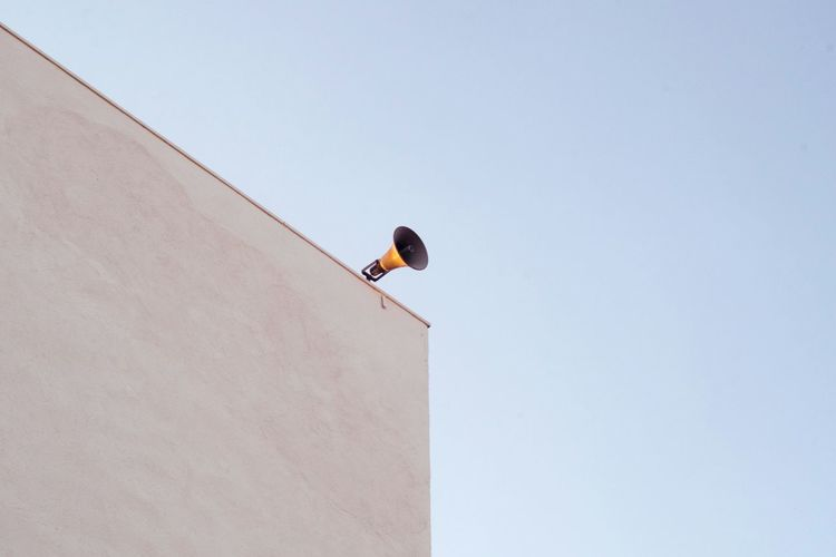 Low angle view of loudspeaker on building terrace against clear sky
