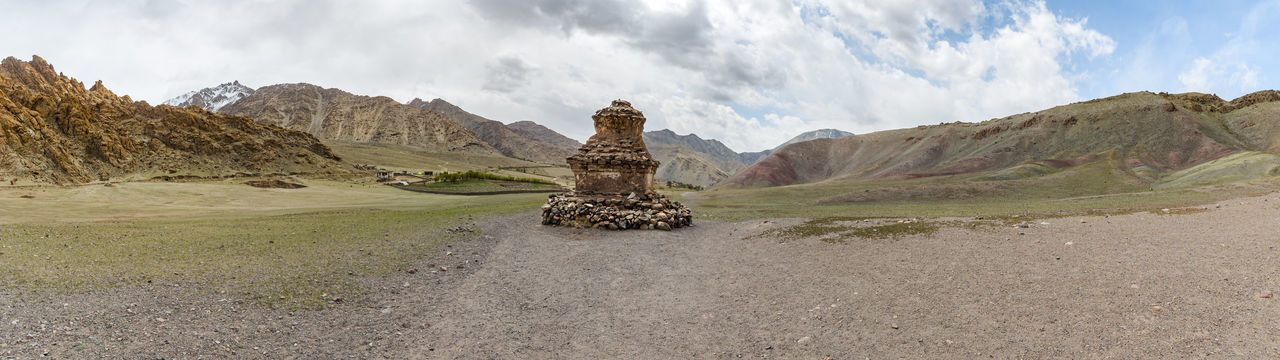 Panoramic view of rock formations on landscape against cloudy sky