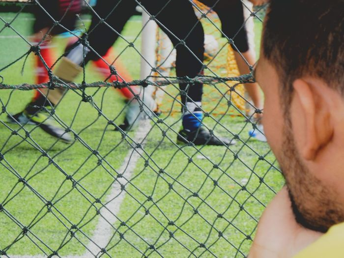 Close-up of man watching soccer through fence