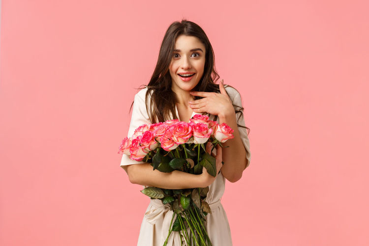 Portrait of smiling woman standing against pink roses