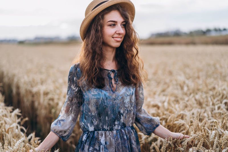 Smiling young woman standing in field
