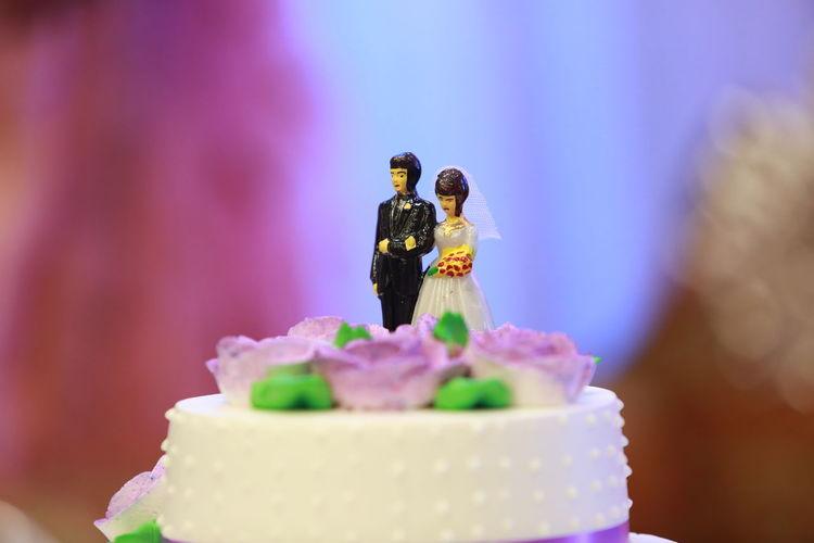 Close-up of figurine on wedding cake