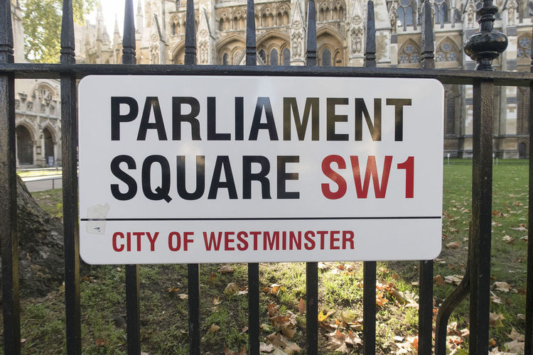 London, United Kingdom - 11 October 2018; Parliament Square street sign in London, in front of the Westminster Abbey a populair tourist location Parliament Square Parliament Square, London London United Kingdom City Of Westminster Westminster Abbey Sign Street Sign Text Fence Outdoors