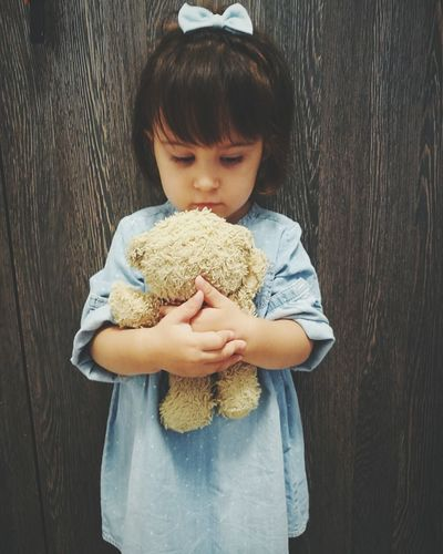 Cute baby girl holding toy while standing against wooden wall