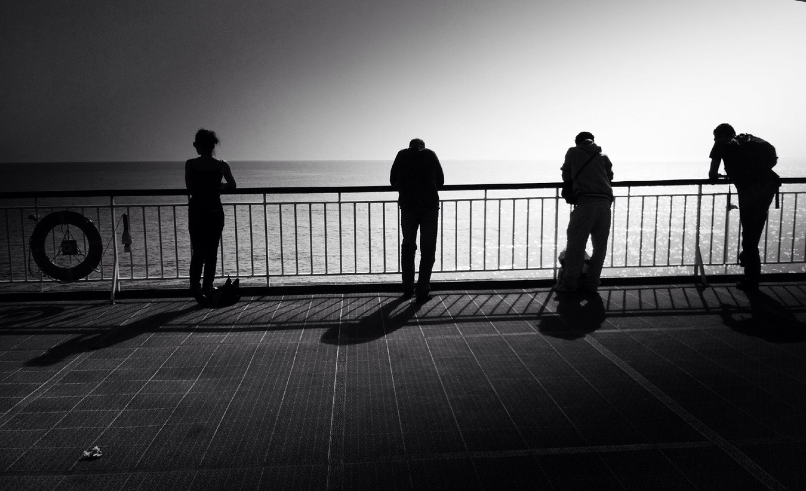 clear sky, men, walking, copy space, transportation, full length, lifestyles, person, silhouette, railing, leisure activity, horizon over water, standing, rear view, sea, shadow, city life, street, travel
