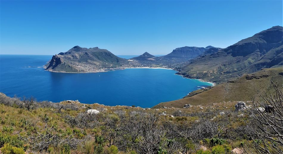 Panoramic view of sea and mountains against clear blue sky