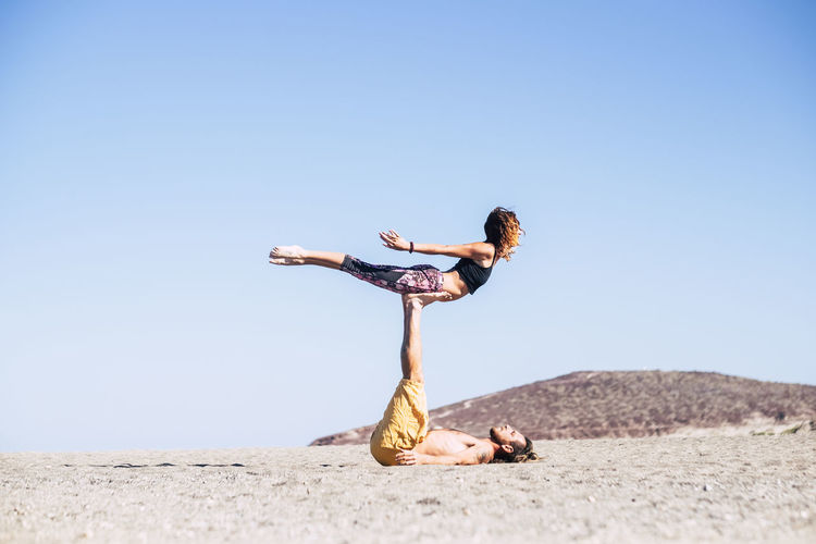 Man practicing acroyoga with female against clear sky