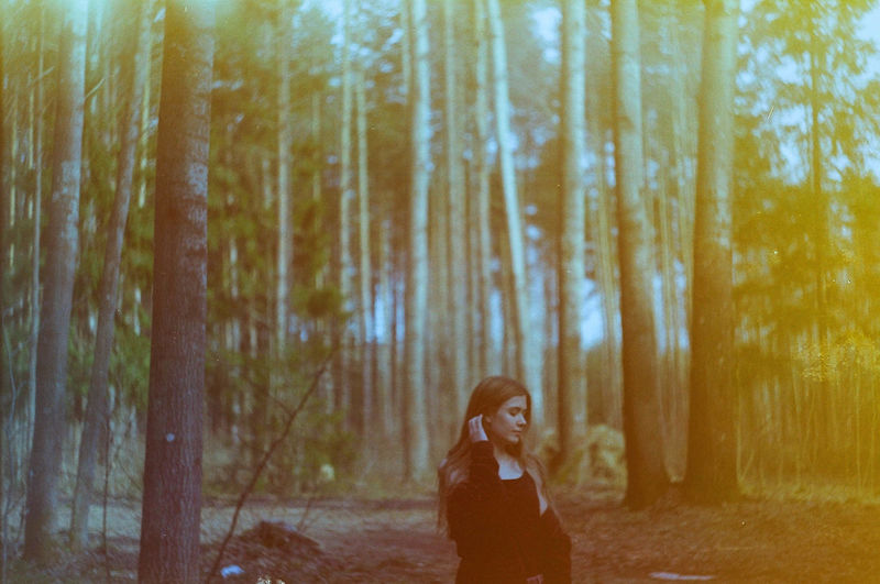 Portrait of woman standing by trees in forest