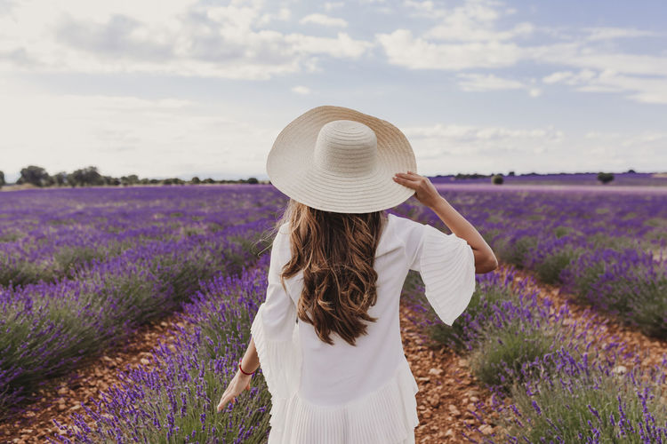 charming Young woman with a hat and white dress in a purple lavender field at sunset. LIfestyle outdoors. Back view Sunset Meadow Beauty Joy Leisure Freedom Farm Herbal Field Gentle Smile Charming Beautiful France Summer Lavender Purple Flower Enjoying Girl Walking Floral Happiness Natural Hat Woman Spring Cheerful Violet Lifestyles Sunny Bloom Passion Aroma Positivity Nature Young Relax Lady Expressing Provence Travel Tenderness Happy Outdoors Harmony Relaxation Blond Caucasian Lifestyle
