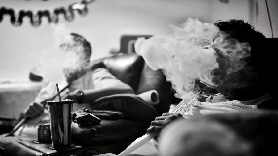 Friends smoking hookah while relaxing on sofa at home