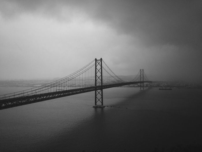 April 25th bridge over tagus river against cloudy sky