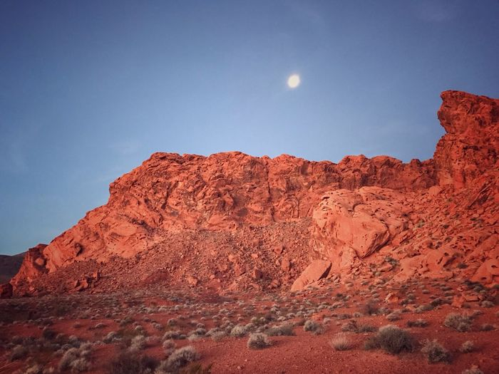 Dawn arrives over red sandstone hillside Moon Beauty In Nature Tranquility Scenics Tranquil Scene Nature Rock Formation Blue Landscape Astronomy Mountain Arid Climate Day Outdoors No People Low Angle View Physical Geography Sky Rock - Object Geology