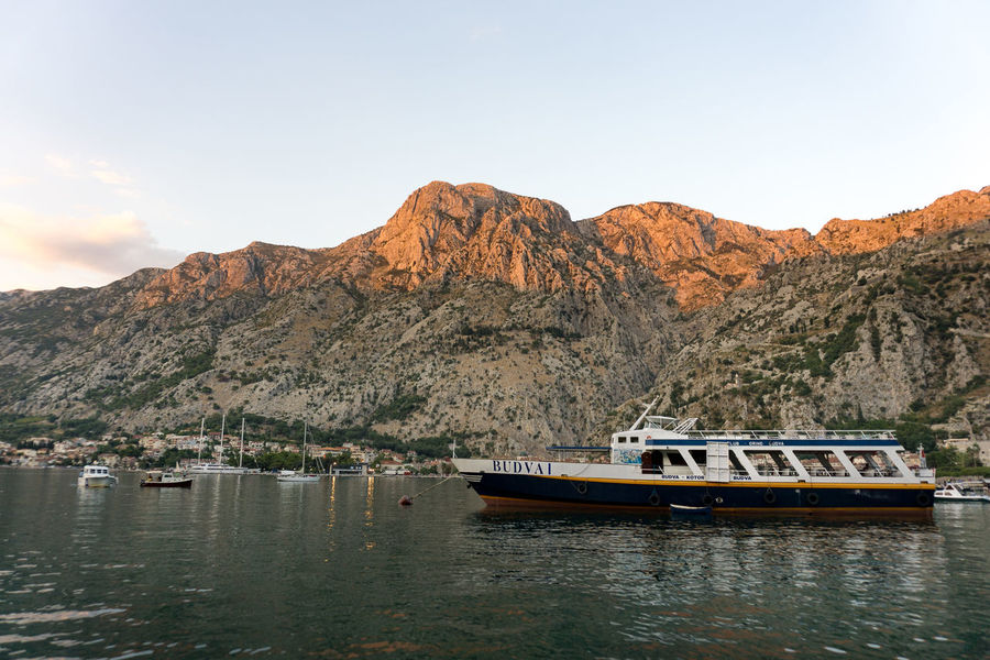 Beauty In Nature Boat Ferry Mode Of Transport Moored Mountain Mountain Range Nature Nautical Vessel No People Non-urban Scene Outdoors Passenger Craft Riverbank Rocky Scenics Sea Sky Town Tranquil Scene Tranquility Transportation Water Waterfront
