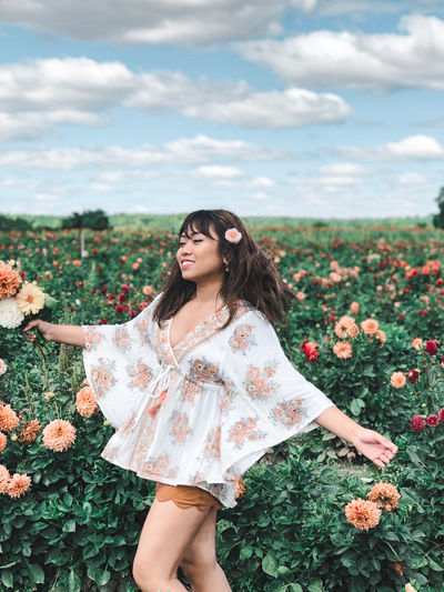 Midsection of woman standing by flowers on field