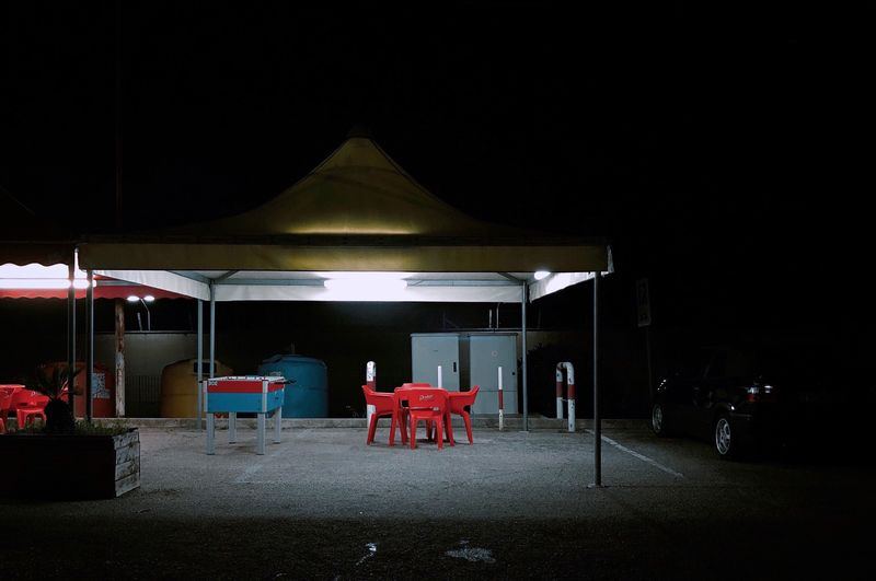 Empty chairs and tables in restaurant at night