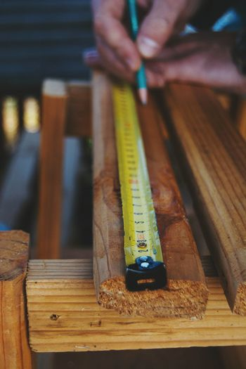 Cropped image of man measuring wooden plank with tape measure