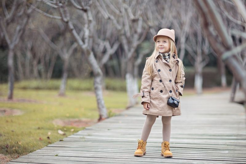 Stylish little girl outdoor. Autumn season Style And Fashion Fall Autumn Kids Stylish Girl Fashionable Fashion Trenches Trench Coat Trenchcoat Trench Childhood One Person Offspring Clothing Child Portrait Full Length Hat Cute Innocence Females Wood - Material Focus On Foreground Nature Front View Women Outdoors Warm Clothing