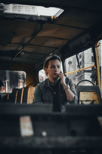 Woman talking on mobile phone while sitting in bus