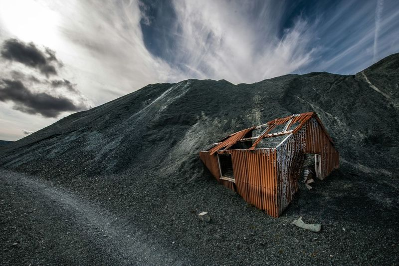 Abandoned hut on mountain against sky
