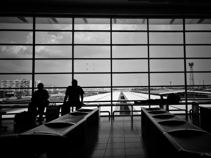 Silhouette people sitting in airport