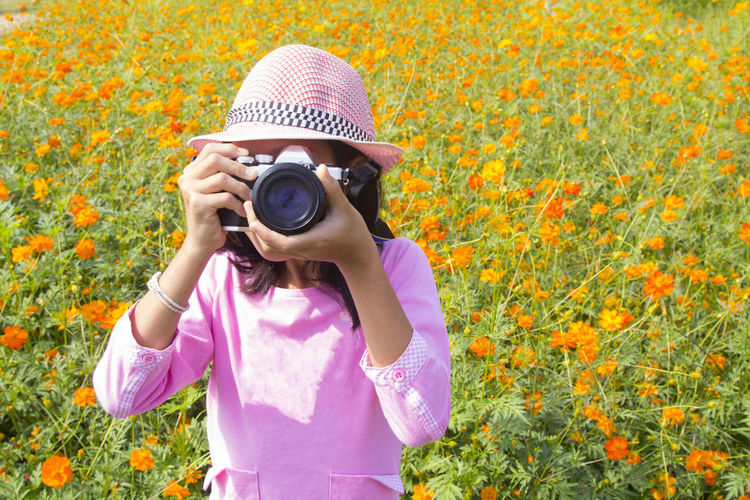 Activity Camera - Photographic Equipment Casual Clothing Day Digital Camera Flower Flowering Plant Front View Holding Leisure Activity Lifestyles Nature Obscured Face One Person Outdoors Photographer Photographic Equipment Photographing Photography Themes Plant Real People Standing Sun Hat Technology