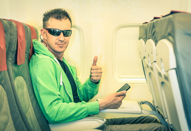 Portrait Of Man Gesturing While Sitting In Airplane