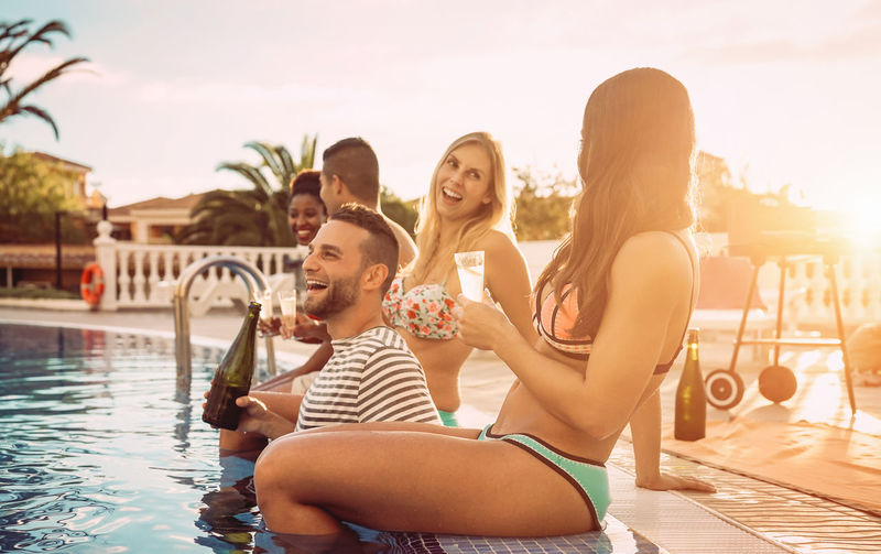 Friends making pool party Happy People Youth Lifestyles Millennials Drinking Champagne Summer Pool Party Swimming Pool Food And Drink Friendship Young Adult Group Of People Water Happiness Holiday Young Women Smiling Trip Sitting Togetherness Nature Outdoors