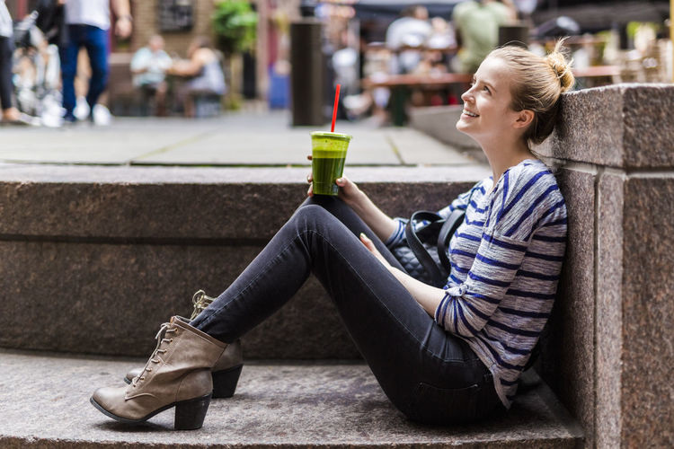 Side view of smiling young woman sitting in city