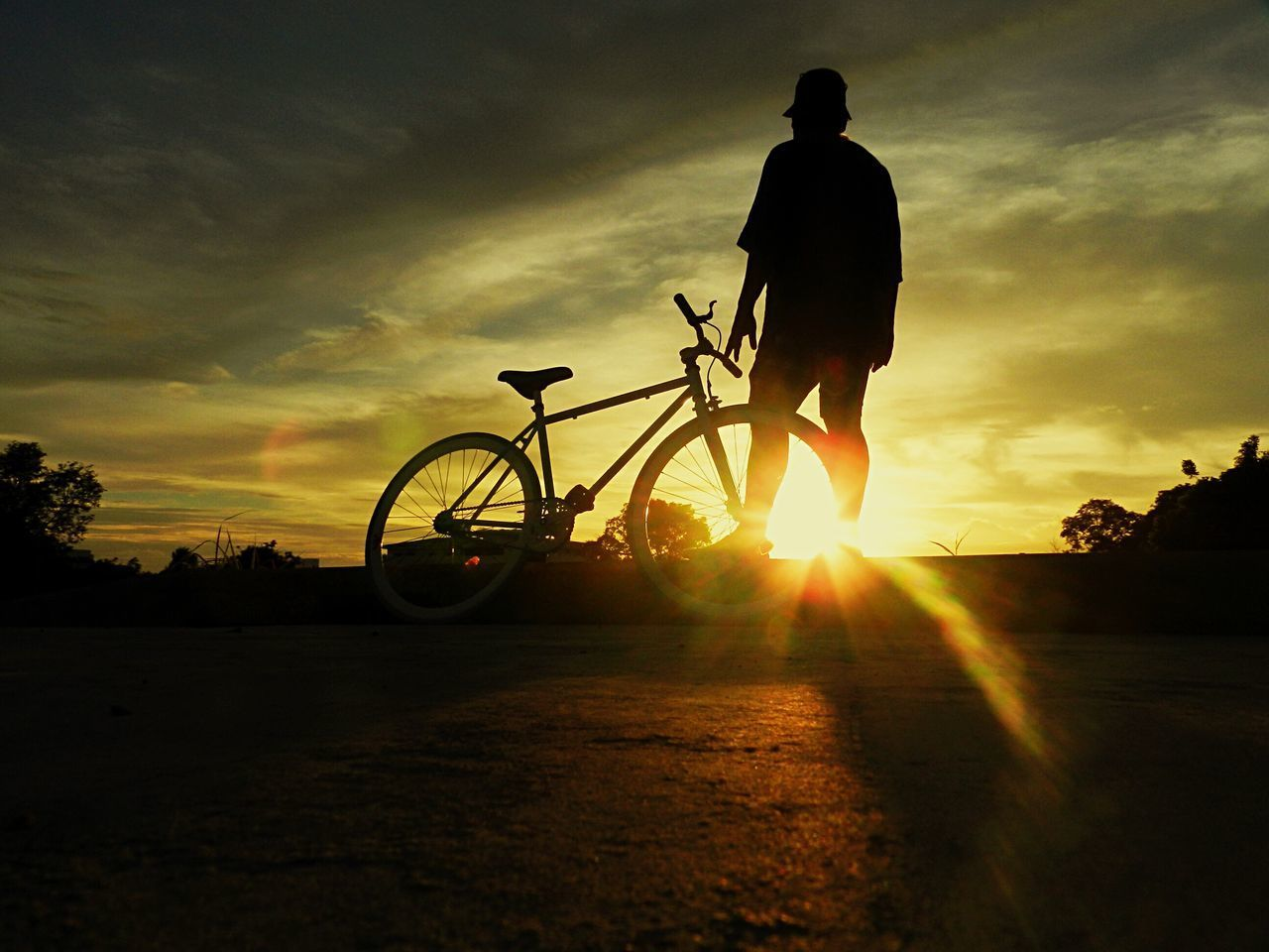 sunset, silhouette, bicycle, sunbeam, sky, sun, real people, transportation, lens flare, sunlight, land vehicle, mode of transport, full length, leisure activity, cloud - sky, cycling, men, one person, lifestyles, nature, outdoors, scenics, beauty in nature, tree, day, people
