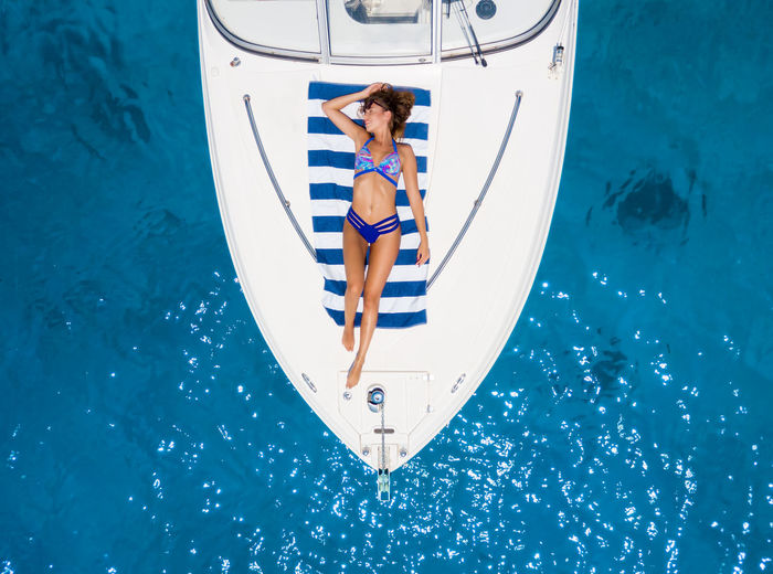 Directly above view of woman in bikini sunbathing on boat