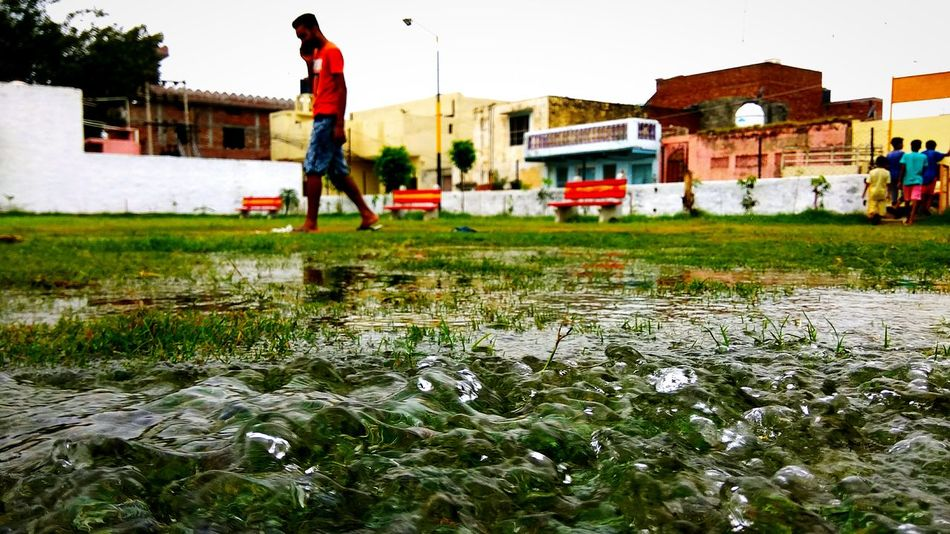 Water over the grass EyeEmNewHere Water Working Spraying Men Occupation Sky Building Exterior Grass Watering Community Garden Planting Gardening