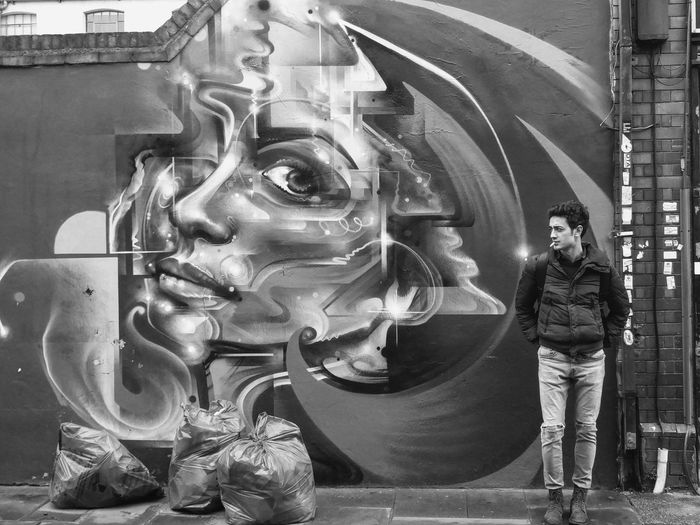Young Man Standing On Street Against Graffiti On Building