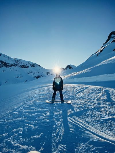 Full length of person on snowcapped mountain against sky during winter