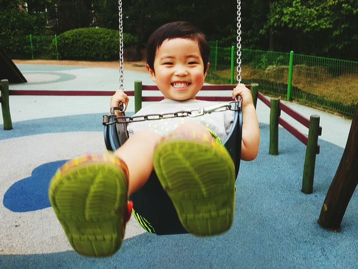 Portrait of smiling boy swinging at playground