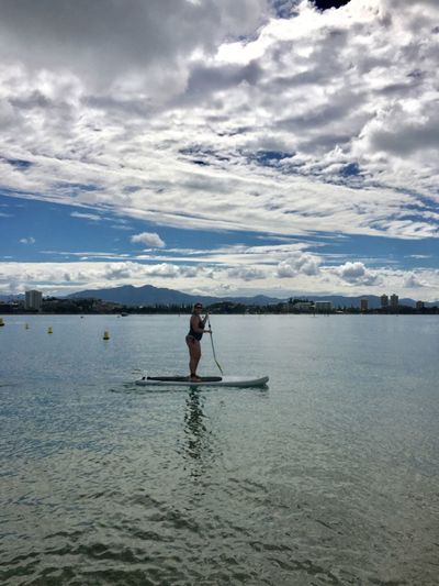 Full length of woman paddleboarding in lake