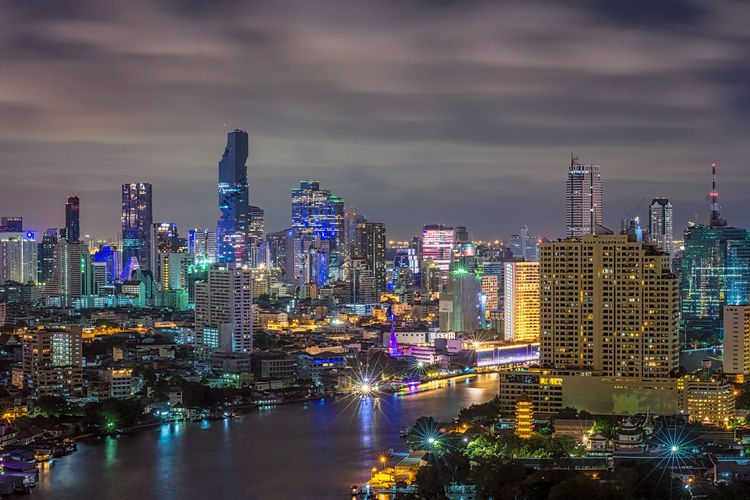 High angle view of chao phraya river amidst illuminated buildings in city