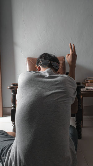 Rear view of young man sitting on wall at home