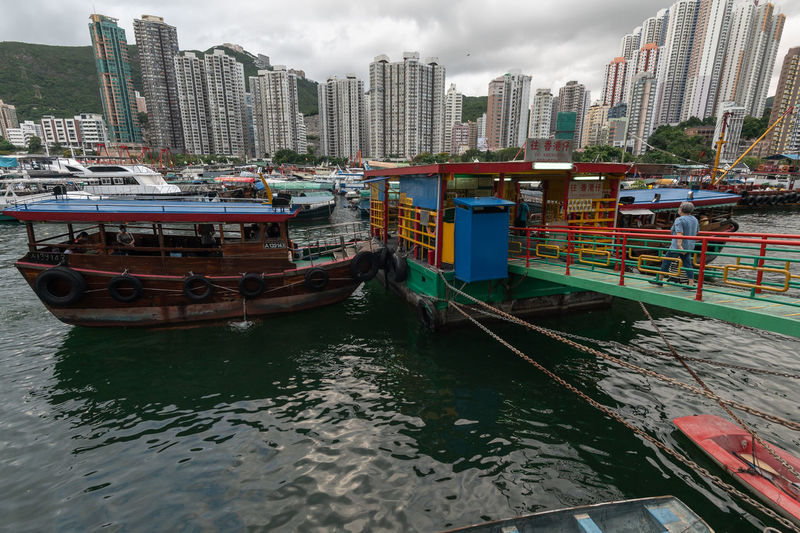Boats moored in river by buildings against sky