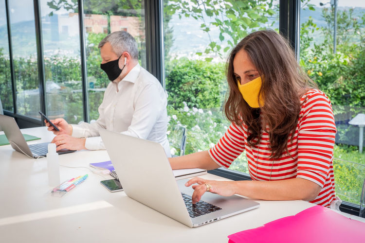 Mature man and woman wearing mask working from home sitting by window