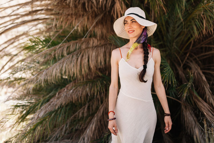 Woman wearing hat while standing against palm trees